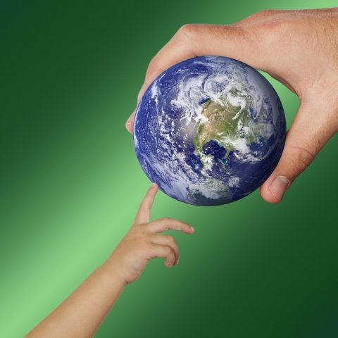 Adult hands earth globe to kid