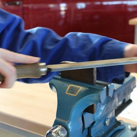 Picture of a worker filing on a piece of metal clamped in a bench vise