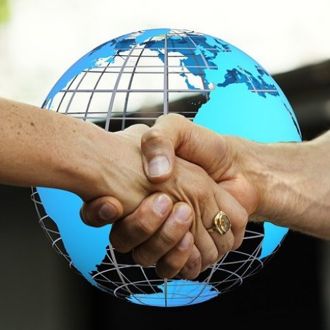 Shaking hands in front of a world globe