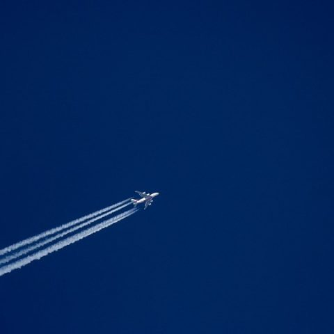 Plane with contrails on blue sky
